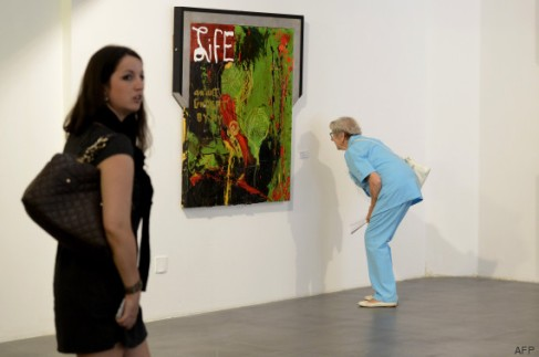 "A woman looks a tag beside an artwork at a retrospective of US actor Sylvester Stallone's  paintings entitled ""Real Love"" Paintings 1975-2015 at the Museum of Contemporary Art in Nice, southeastern France, on May 16, 2015.  AFP PHOTO / FRANCK PENNANT = RESTRICTED TO EDITORIAL USE, MANDATORY MENTION OF THE ARTIST UPON PUBLICATION, TO ILLUSTRATE THE EVENT AS SPECIFIED IN THE CAPTION ="
