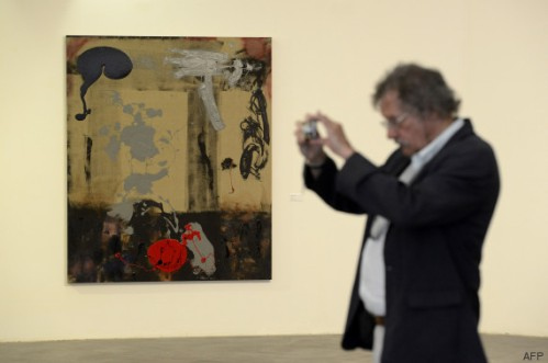 "A man takes a photo next to an artwork at a retrospective of US actor Sylvester Stallone's  paintings entitled ""Real Love"" Paintings 1975-2015 at the Museum of Contemporary Art in Nice, southeastern France, on May 16, 2015.  AFP PHOTO / FRANCK PENNANT = RESTRICTED TO EDITORIAL USE, MANDATORY MENTION OF THE ARTIST UPON PUBLICATION, TO ILLUSTRATE THE EVENT AS SPECIFIED IN THE CAPTION ="